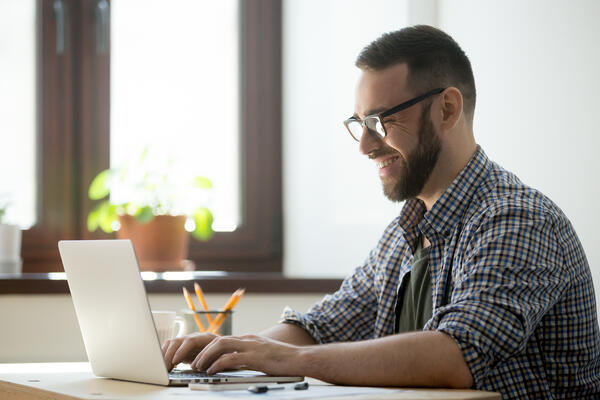 a male employee moderating on an online focus group discussion in front of his laptop