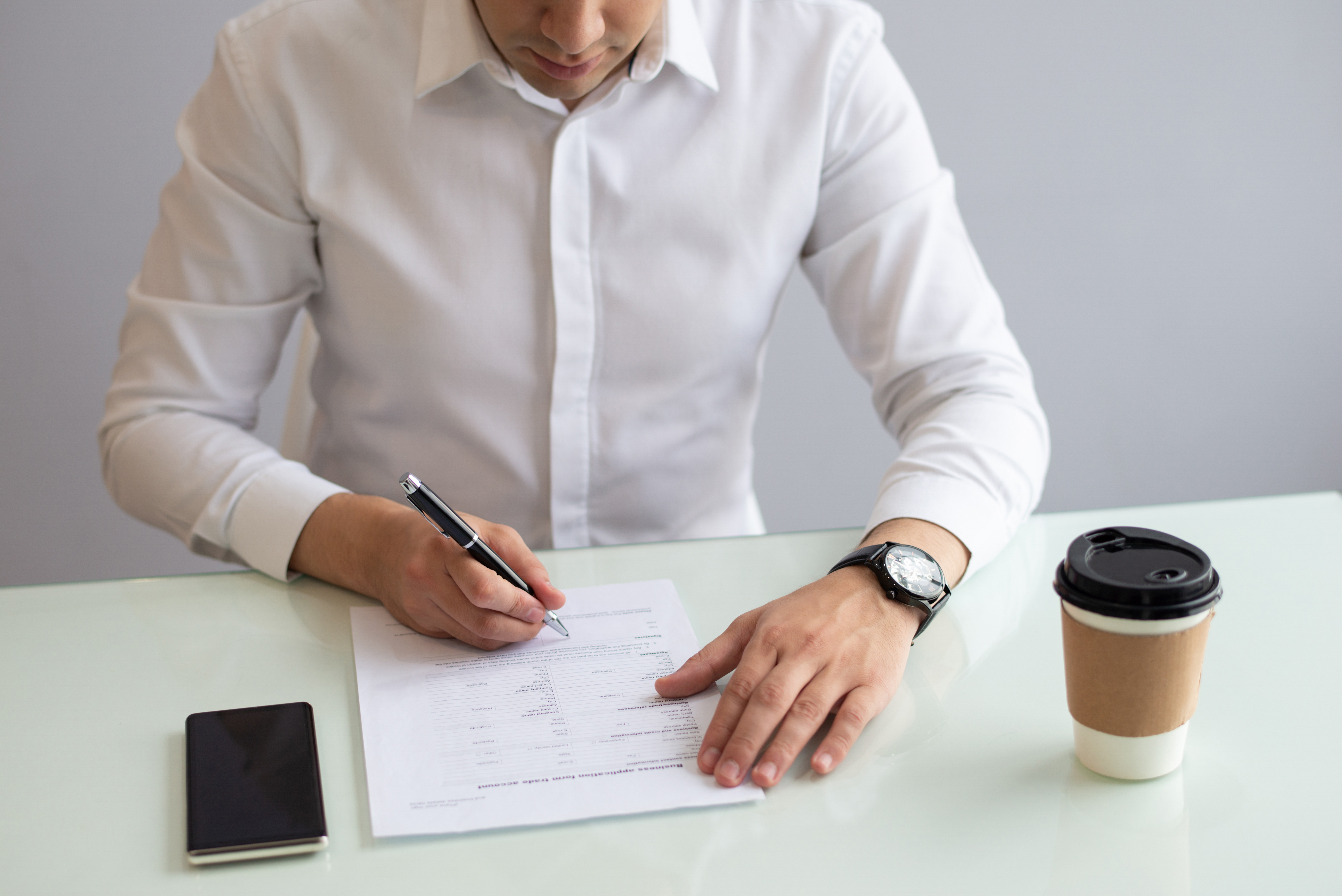 a male employee filling up a market research survey on a desk with his phone and coffee